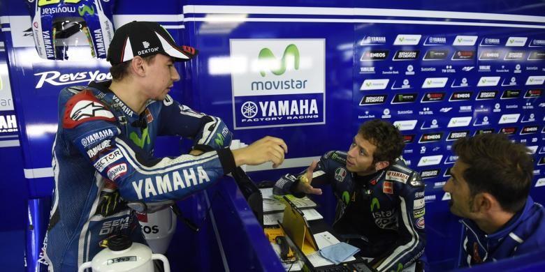 Pebalap Movistar Yamaha asal Italia, Valentino Rossi (tengah) berdiskusi dengan rekan satu timnya, Jorge Lorenzo (kiri), saat sesi kualifikasi GP Aragon di Sirkuit Motorland, Sabtu (27/9/2014).