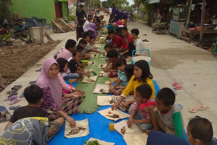 Warga di Banten menggelar makan bersama sebagai wujud syukuran atas diperbaikinya jalan rusak yang dinantkan mereka selama 70 tahun, Jumat (3/7/2020).