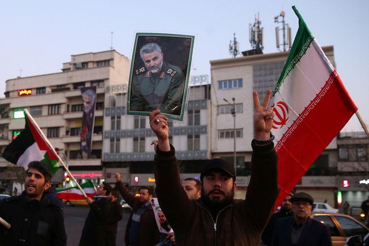 Seorang pria memegang gambar mendiang Komandan Pasukan Quds, Mayor Jenderal Qasem Soleimani, di tengah perayaan setelah Iran melancarkan serangan rudal terhadap pangkalan AS di Irak pada 8 Januari 2020. Serangan itu merupakan balasan setelah AS membunuh Soleimani pekan lalu.