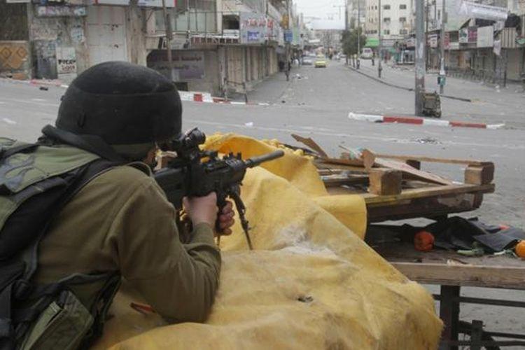Seorang prajurit Israel tengah mengarahkan senjatanya dalam sebuah bentrokan dengan warga Palestina di kota Hebron, Tepi Barat pada 17 Maret 2014, menyusul aksi unjuk rasa warga yang mendukung Presiden Mahmoud Abbas.