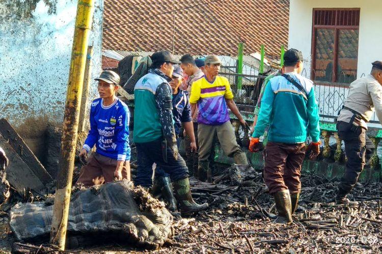 Sejumlah relawan saat membersihkan tumpulan lumpur dan kayu yang terbawa banjir di Kecamatan Ijen Kabupaten Bondowoso