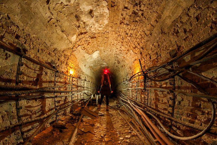 Ilustrasi urbex people menjelajahi terowongan bawah tanah yang telah terbengkalai.