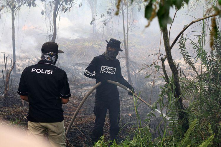 Petugas kepolisian dari Polresta Pontianak bersama pemadam kebakaran swasta saat berupaya memadamkan api di lahan gambut yang mendekati permukiman warga di Jalan Purnama II, Pontianak (20/8/2018).