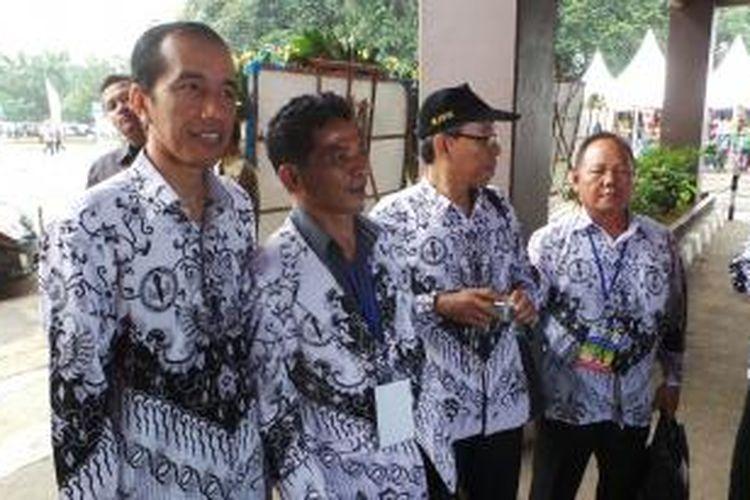 Gubernur DKI Jakarta Joko Widodo (kiri) berfoto bersama guru dari PGRI di Istora Senayan, Jakarta, Rabu (3/7/2013).