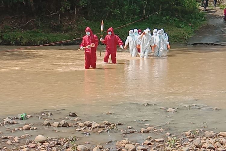 SEBERANGI SUNGAI—Tim pemakaman jenazah pasien covid-19 Kabupaten Wonogiri harus menyebarangi sungai menuju lokasi pemakaman di Desa Mojopura, Kecamatan Jatiroto, Kabupaten Wonogiri, Jawa Tengah, Rabu (23/6/2021).
