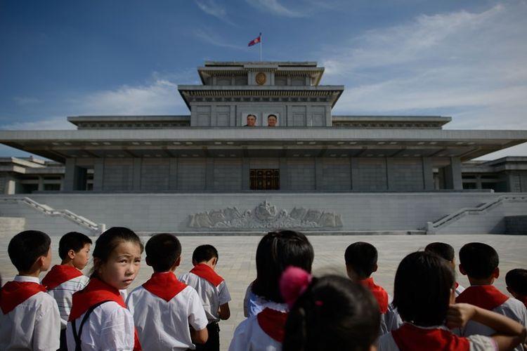 Anak-anak Korea Utara berkumpul di depan foto pemimpin negara Kim Il-Sung and Kim Jong-Il di Istana Kumsusan di Pyongyang pada Juli 2013 lalu.
