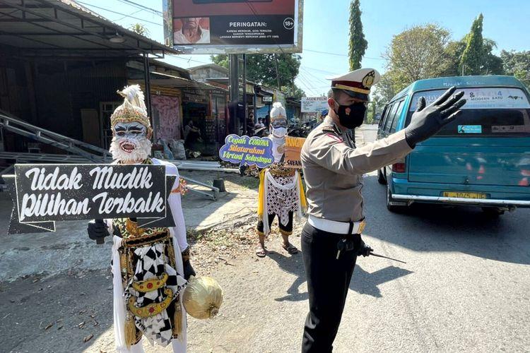 Anggota komunitas seni wayang orang terlibat pada kegiatan petugas di pos penyekatan Karangkates di jalur yang menghubungkan wilayah Kabupaten Blitar dan Kabupaten Malang, Senin (10/5/2021)