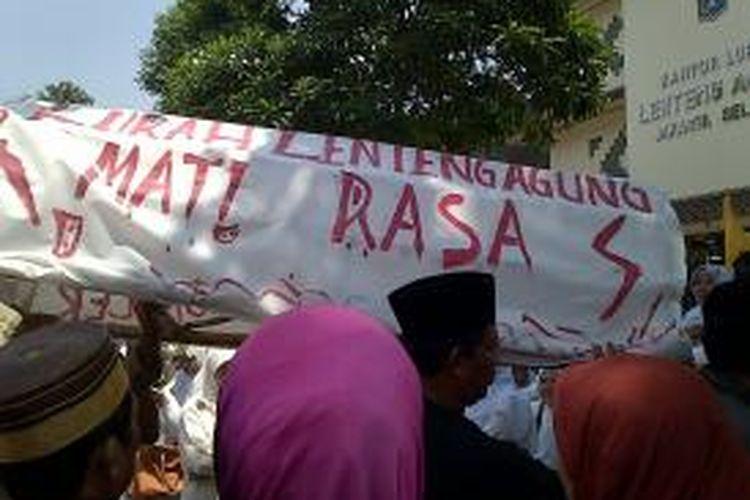 Para warga yang melakukan aksi damai di depan Kantor Lurah Lenteng Agung di akhir aksinya, menyerahkan keranda yang di bawa dalam aksi ke Kelurahan. Mereka memaksa Lurah Susan Jasmine Zulkifli untuk menerima keranda tersebut, namun akhirnya keranda di terima oleh Kapolsek Jagakarsa, Kompol Herawaty, Jakarta selatan, Rabu (25/9/2013)