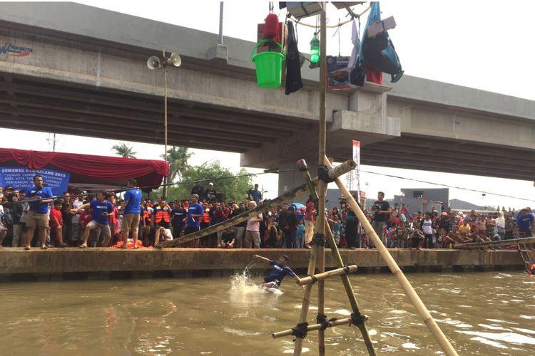 Dwi, Salah satu peserta lomba panjat pinang, di Jalan Raya Kalimalang, Jakarta Timur, Jumat (17/8/2018).