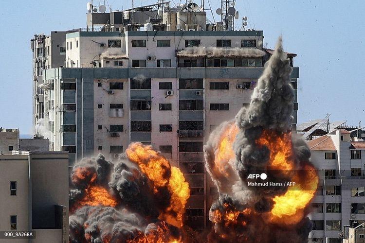 Bola api mengepul dari Menara Jala, setelah dihancurkan oleh militer Israel di Gaza City, yang dikuasai faksi Palestina Hamas, pada 15 Mei 2021. Serangan udara terbaru Israel menewaskan 10 anggota keluarga dan dua kantor media. Milisi Palestina menembakkan roket sebagai balasan.