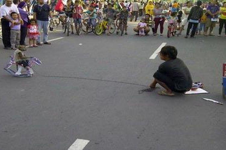 Atraksi topeng monyet saat hari bebas kendarabn bermotor di salah satu jalan di Semarang, Minggu (17/3/2013).