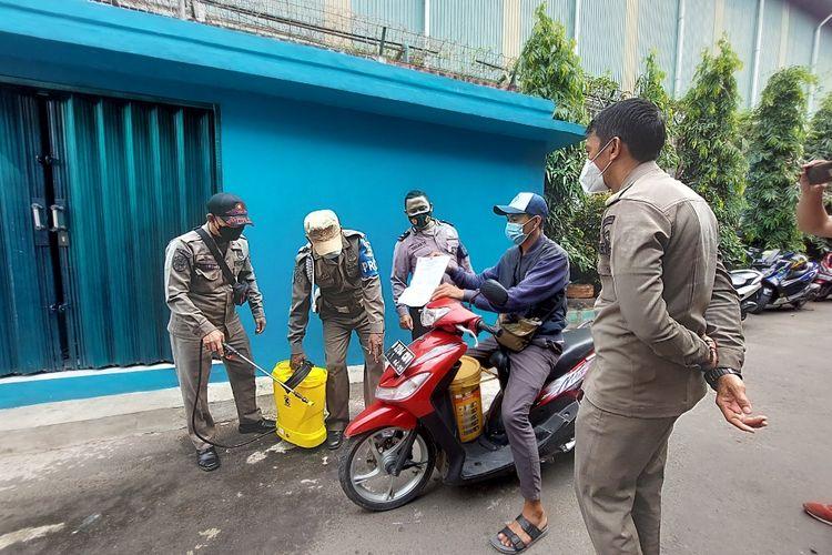 Salah seorang pengendara motor yang hendak memasuki RT01/RW03, Gandasari, Jatiuwung, Kota Tangerang, diminta menunjukkan surat hasil negatif tes antigen kepada petugas yang berjaga, pada Kamis (10/6/2021).