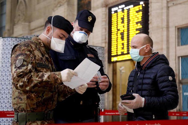 Polisi dan petugas militer melakukan pengecekan di Stasiun Pusat, Milan, Italia, 20 Maret 2020. Pengecekan dilakukan untuk memastikan warga yang bepergian tidak melanggar aturan karantina.