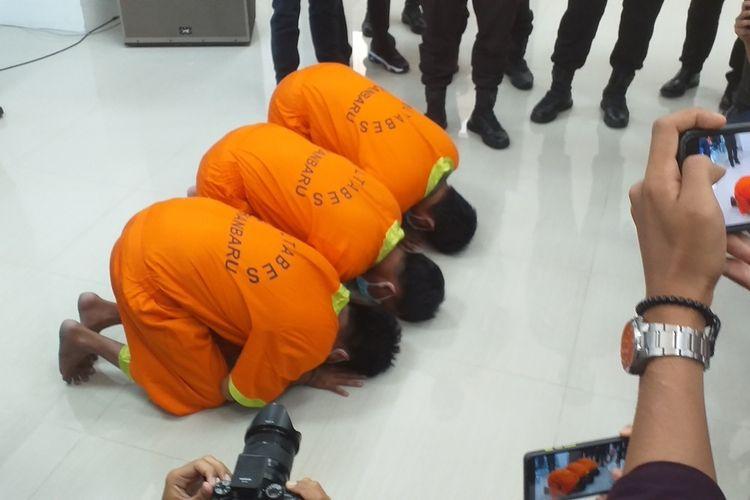 Tiga pelaku teror pelemparan potongan kepala anjing dan penyiraman bensin, IP, DW, KO, bersujud meminta maaf saat dihadirkan dalam konferensi pers di Mapolda Riau di Jalan Pattimura, Kota Pekanbaru, Riau, Jumat (12/3/2021).