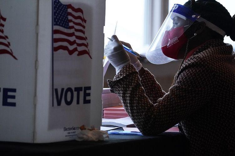 Seorang petugas pemungutan suara berbicara kepada pemilih sebelum mereka memberikan suara pada Hari Pemilihan di Atlanta pada hari Selasa, 3 November 2020.