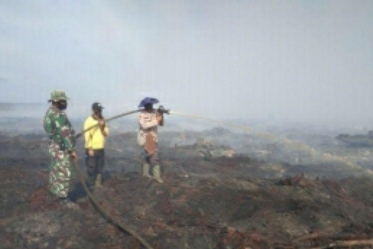 Tim satgas memadamkan titik api karhutla di wilayah Kabupaten Bengkalis, Riau, Senin (22/2/2021).