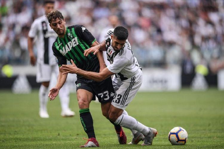 Manuel Locatelli dan Emre Can berduel dalam laga Juventus vs Sassuolo pada lanjutan Serie A di Turin, 16 September 2018.