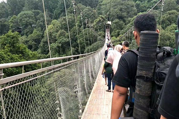 Wisatawan melintasi Suspesion Bridge yang terletak di kawasan wisata Situ Gunung, Sukabumi, Jawa Barat, Minggu (13/1/2019).