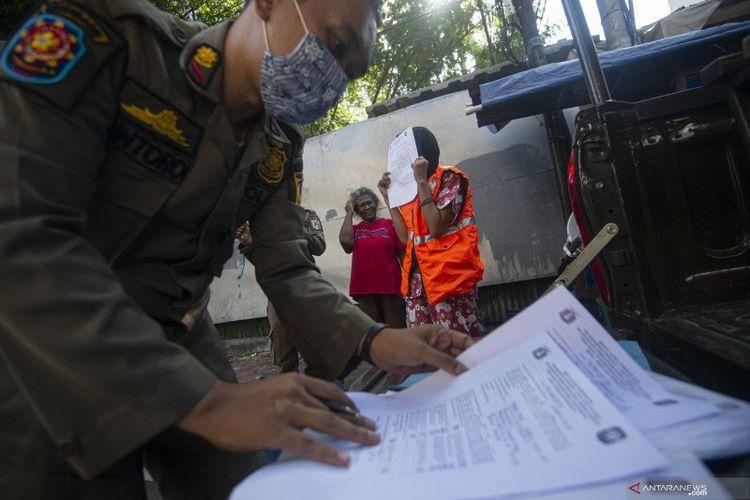 Petugas Satpol PP mendata warga yang melanggar aturan protokol kesehatan COVID-19 selama masa Pembatasan Sosial Berskala Besar (PSBB) transisi di kawasan Juanda, Jakarta, Jumat (21/8/2020).