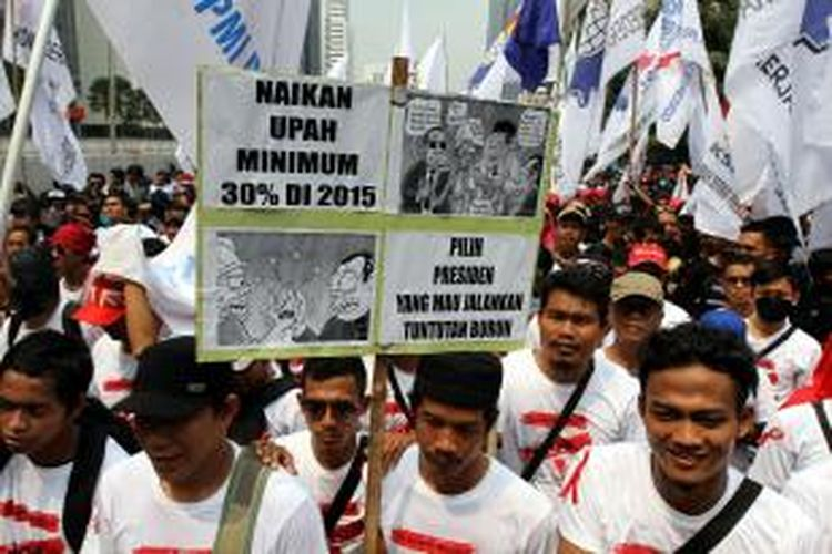 Ribuan buruh dari berbagai organisasi berunjuk rasa memperingati Hari Buruh Internasional, melintasi Jalan MH Thamrin, Jakarta Pusat, Kamis (1/5/2014). Hari Buruh Internasional ditetapkan sebagai hari libur nasional untuk kali pertama di tahun ini, diperingati dengan berunjuk rasa menuntut upah layak, penghapusan outsourcing, dan penolakan terhadap undang-undang Badan Penyelenggara Jaminan Nasional. TRIBUNNEWS/HERUDIN