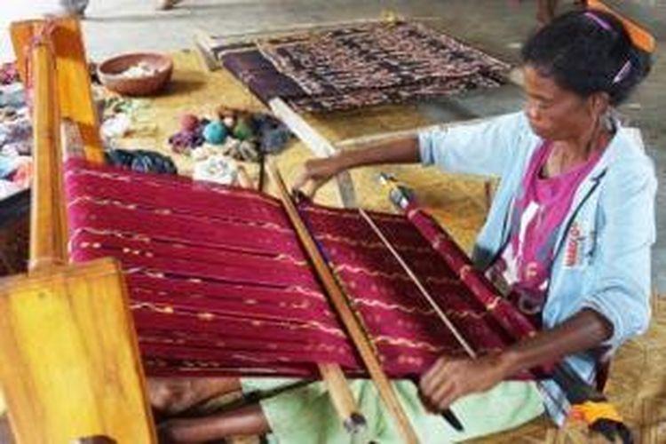 Seorang perajin tenun tengah menenun dengan alat tenun tradisional gedogan di Kampung Hula, Desa Alor Besar, Kabupaten Alor, Nusa Tenggara Timur.