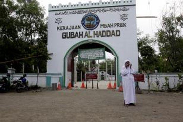 Seorang peziarah keluar dari area makam Habib Hasan Al Haddad atau Mbah Priok yang berada di dekat terminal peti kemas PT Pelindo II, Koja, Jakarta Utara, Senin (8/3/2010). Pemerintah kota Jakarta Utara berencana melakukan penataan lahan pemakaman tersebut untuk pengembangan terminal peti kemas.