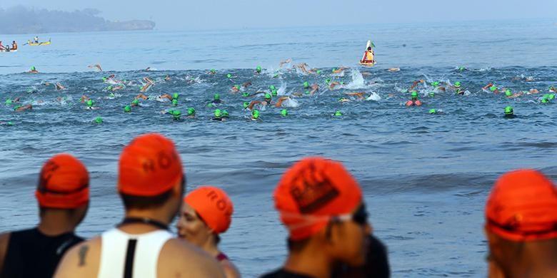 Peserta Herbalife Bali International Triathlon (HBIT) 2015 berenang melintasi rute yang telah ditentukan di kawasan Pantai Jimbaran, Bali, Minggu (25/10/2015).