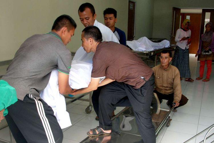 Petugas medis mengangkat jenazah korban yang meninggal akibat meminum minuman keras (miras) jenis oplosan, di sebuah rumah sakit di Bandung, Jawa Barat, Senin (9/4/2018). Korban miras jenis oplosan di daerah tersebut terus bertambah, dari data terakhir sebanyak 23 orang dilaporkan tewas dengan indikasi keracunan.