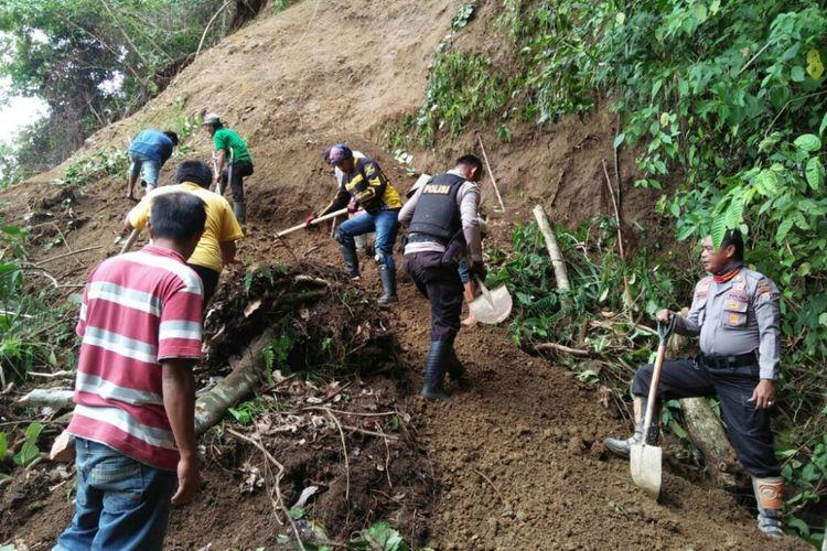 Aparat Polsek Bastem dan warga sekitar berupaya memindahkan runtuhan longsor yang menutupi akses Jalan Trans Sulawesi.