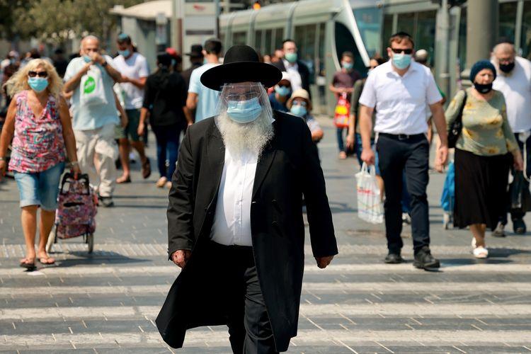 Seorang pria Yahud Ultra Ortodox mengenakan masker dan pelindung muka (face shield) tengah berjalan di jalanan Yerusalem pada 11 September 2020. Israel pada pekan ini bakal menerapkan lockdown kedua sebagai bagian dari membendung peningkatan kasus virus corona.