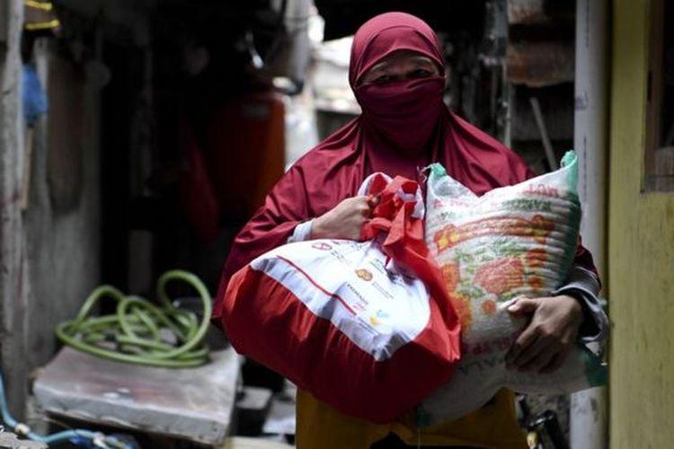 Warga membawa paket bantuan sosial dari pemerintah yang ia terima di kawasan Koja, Jakarta, Sabtu (02/05).