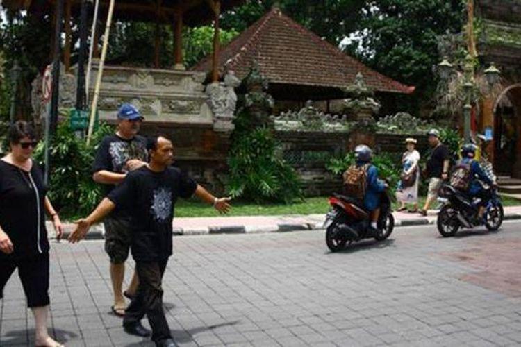 Seorang pemandu wisata membawa turis berkeliling Ubud, Gianyar, Bali.