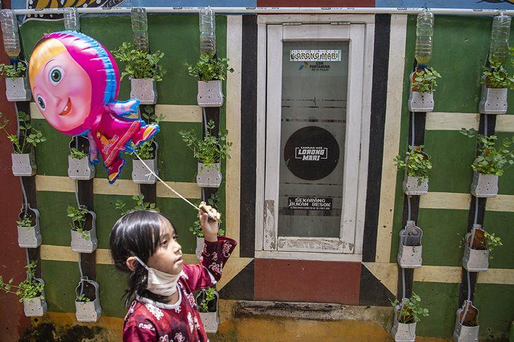 Foto dirilis Jumat (6/11/2020), memperlihatkan seorang bocah bermain di kampung tangkal COVID-19 Lorong Mari, Talang Bubuk, Plaju, Palembang, Sumatera Selatan. Satgas Ayam Jago melibatkan seluruh elemen masyarakat di daerah setempat dengan tujuan untuk menanggulangi wabah dan memutus rantai penyebaran Covid-19.