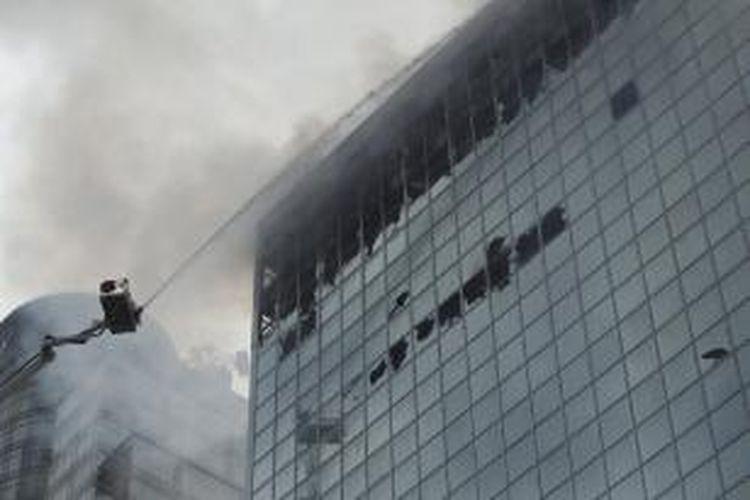 Petugas pemadam kebakaran berusaha memadamkan api di gedung Wisma Kosgoro, di Jalan MH Thamrin, Jakarta, Selasa (10/3/2015). Kebakaran yang terjadi pada Senin malam ini bermula dari lantai 16 dan merembet ke lantai 20. Penyebab kebakaran masih ditelusuri.