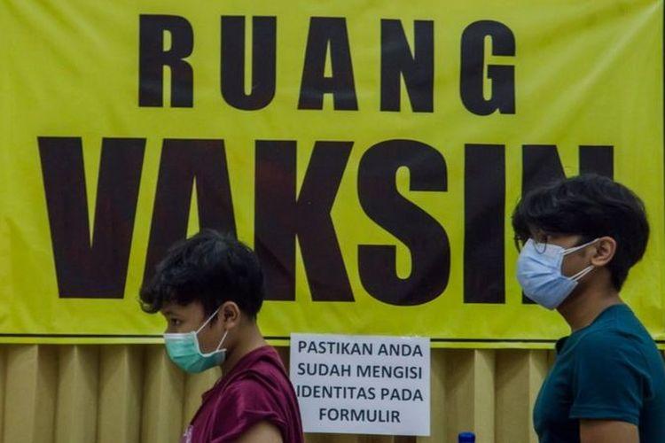Dua anak berusia 12-17 tahun mengantre untuk vaksinasi massal COVID-19 di Kampus Itenas, Bandung, Jawa Barat, Jumat (23/7/2021)