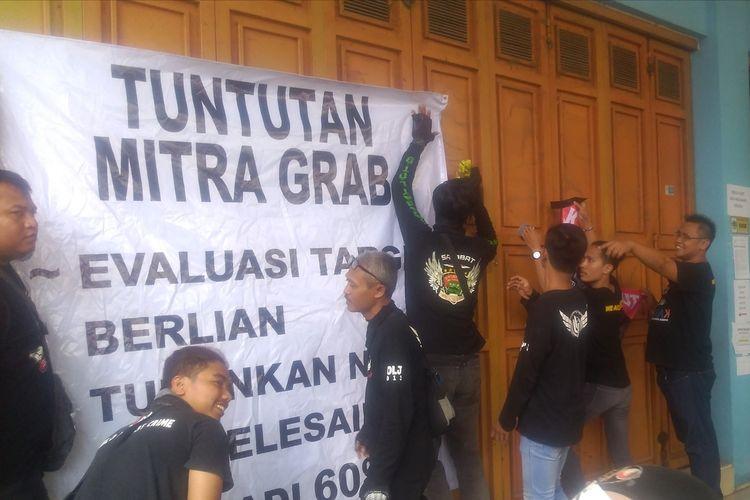 Pengemudi ojol yang tergabung dalam Driver Ojol Banyumas Raya Kompak memasang spanduk tuntutan di depan kantor Grab Jalan Kolonel Sugiono Purwokerto, Jawa Tengah, Rabu (21/8/2019).
