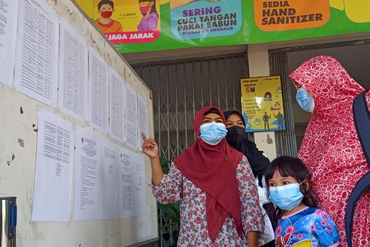Para orangtua melihat pengumuman hasil Penerimaan Peserta Didik Baru (PPDB) 2021 di SMAN 1 Depok, Sleman, DIY, Jumat (2/7/2021).