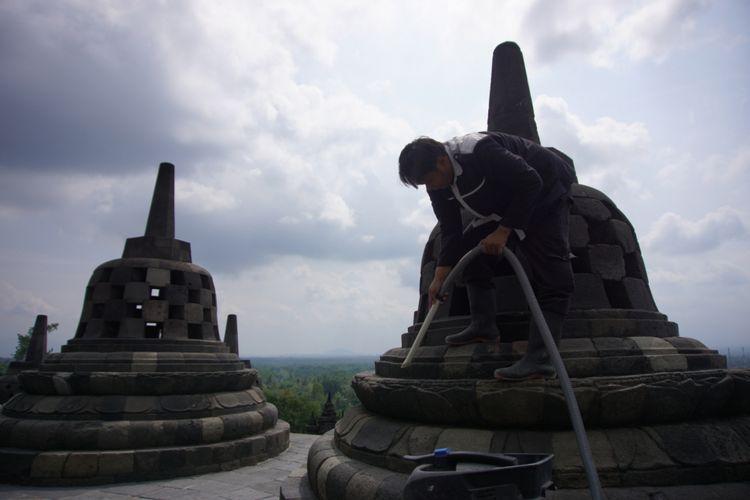 Seorang petugas membersihkan abu vulkanik Gunung Merapi yang menempel di stupa candi Borobudur, Kamis (24/5/2018),