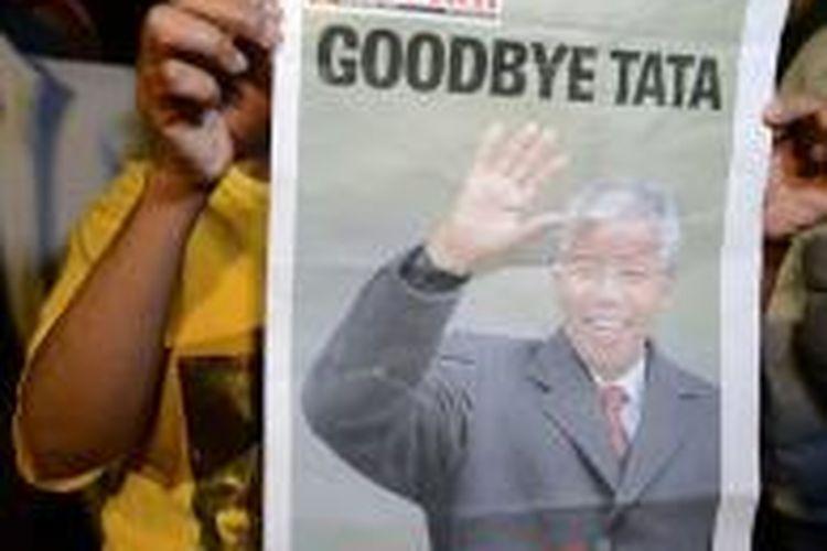 Seorang warga yang turut berduka memegang sebuah koran pada malam doa di luar rumah Mandela.