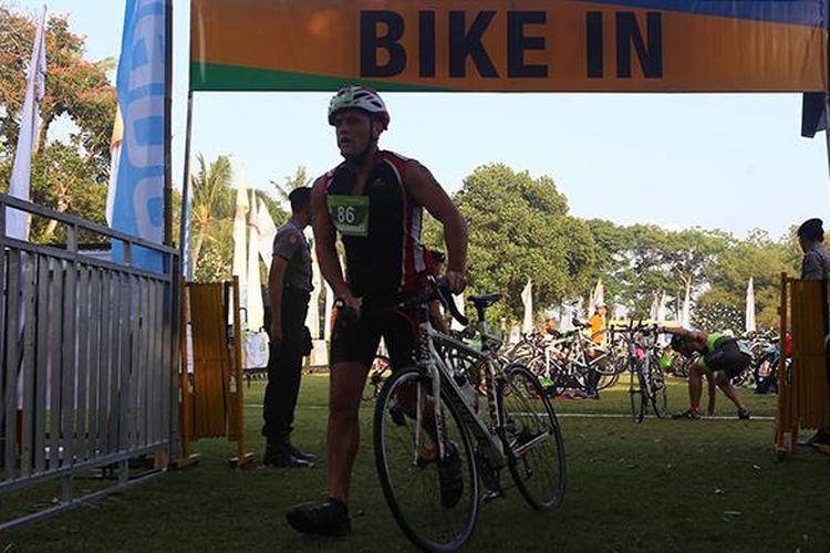 Peserta Herbalife Bali International Triathlon (HBIT) 2015 bersepeda menuju jalur yang telah ditentukan di kawasan Pantai Jimbaran, Bali, Minggu (25/10/2015).