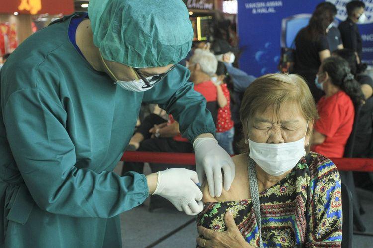 Seorang lansia sedang disuntik vaksin Covid-19 oleh seorang petugas medis. Sebelumnya, Pemerintah kota Palembang membuka Vaksinasi massal untuk lansia yang berusia 60 tahun ke atas di mall Palembang Icon (Picon), Selasa (16/3/2021). Vaksinasi ini diikuti oleh ratusan lansia yang telah mendaftar secara online.