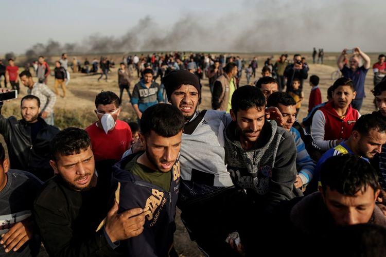 Para pengunjuk rasa membopong rekan mereka yang terluka saat bentrokan dengan pasukan Israel di perbatasan Israel dan Palestina di Jalur Gaza, Rabu (4/4/2018).