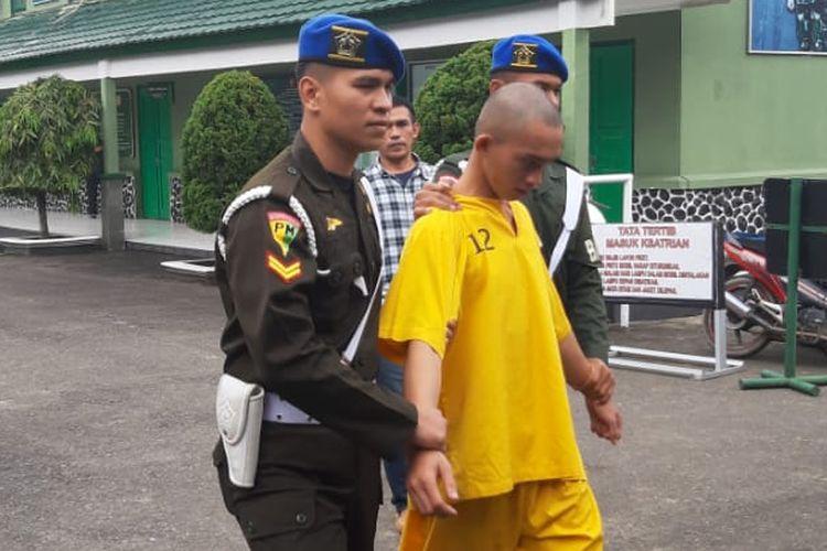Prada DP dikawal anggota Denpom II Sriwijaya setelah ditangkap petugas. Prajurit baru ini ditangkap atas kasus pembunuhan serta mutilasi terhadap pacarnya sendiri, Jumat (14/6/2019).