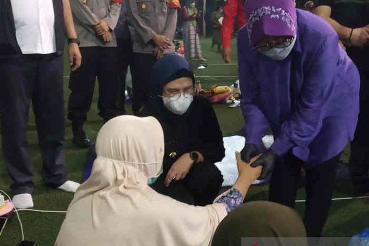 Menteri Sosial (Mensos) Tri Rismaharini (kanan) saat memijat tangan pengungsi korban kebakaran kilang Pertamina Balongan.