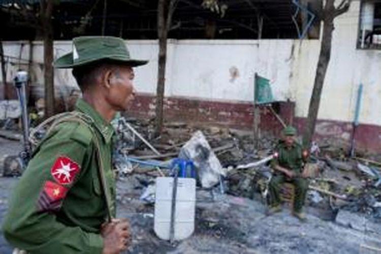 Tentara berjaga di depan masjid yang dibakar di Lashio, Shan, utara Myanmar, 29 Mei 2013. Pemerintah Myanmar menyerukan masa tenang setelah massa membakar sebuah panti asuhan muslim, sebuah masjid dan toko-toko dalam kerusuhan agama di timur negara itu.
