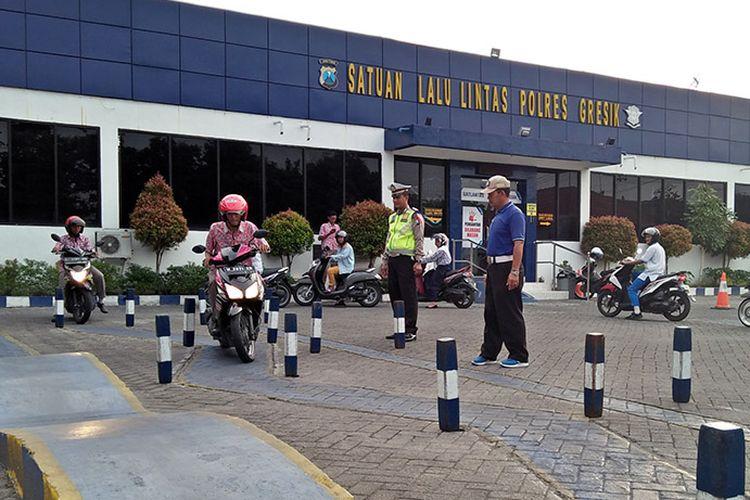 Aiptu Jailani (tengah) saat memberi pelatihan kepada pemohon SIM di halaman Satlantas Polres Gresik.