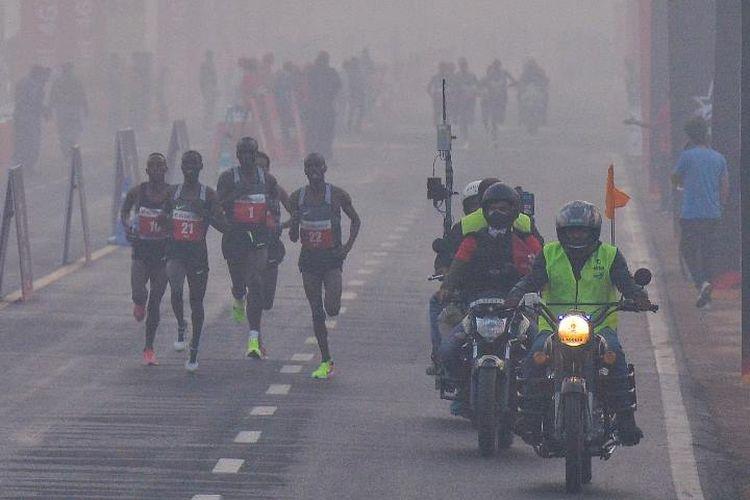 Peserta Maraton di New Delhi, India, berlari menembus asap polusi di jalan, Minggu (19/11/2017). (The Guardian)