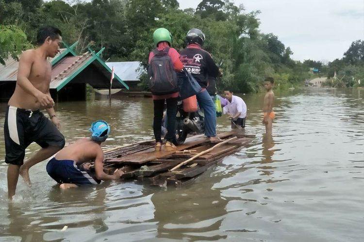 Warga terpaksa menyeberangkan sepeda motor dengan rakit di daerah Karang Taba-Sungai Tuat, akibat banjir yang membuat Jalan Trans Kalimantan putus di wilayah Kabupaten Lamandau
