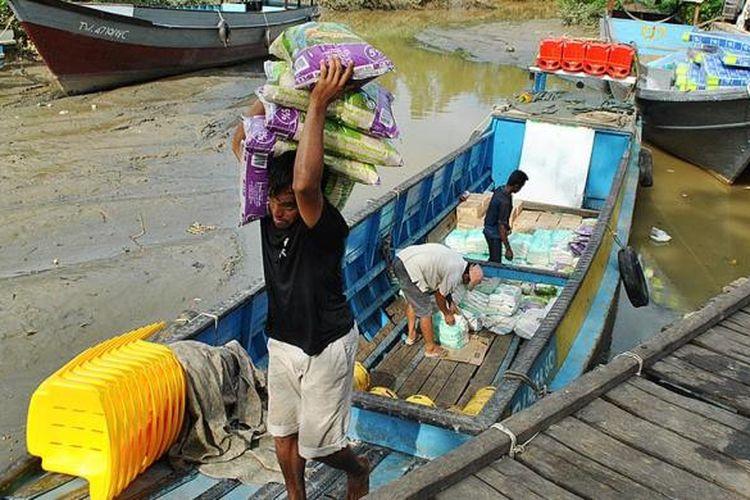 Suasana bongkar muatan perahu di Dermaga Lalo Salo, Pulau Sebatik, Nunukan, Kalimantan Utara, Rabu (21/12/2016). Sekitar 70 persen kebutuhan warga Sebatik didatangkan dari Tawau, Malaysia. Barang-barang ini masuk secara ilegal, dan kondisi ini sudah berlangsung bertahun-tahun.