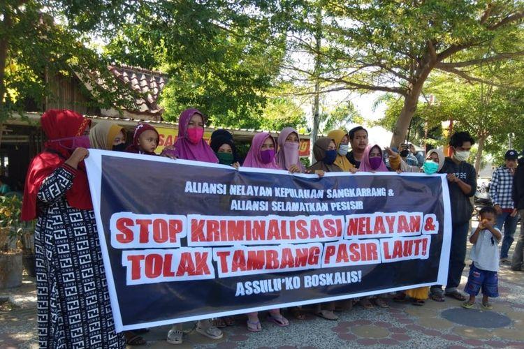 Beberapa ibu-ibu dari Pulau Kodingareng Lompo, Makassar, saat membentangkan spanduk upaya kriminalisasi nelayan yang menolak tambang pasir di depan kantor Polairud Polda Sulsel, Senin (3/8/2020).